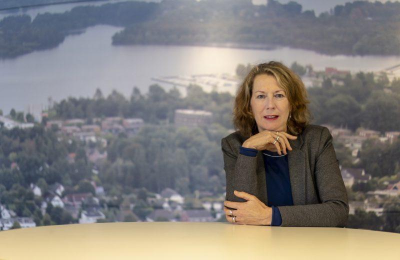 Mirjam Kuin, directeur van WIJ Groningen, zit voor een luchtfoto van Groningen.
