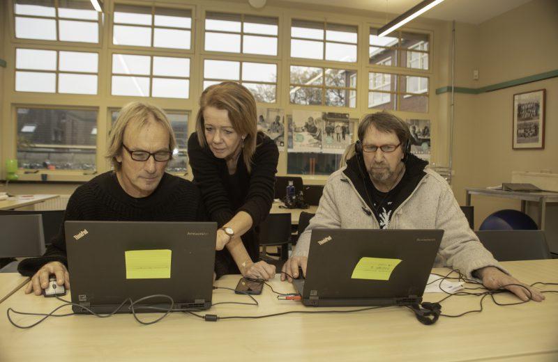 Henk en Henk zittend achter de laptop met begeleider Regina die wijst naar één van de schermen