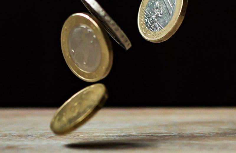 Euromunten van dichtbij vlak voordat ze op een tafel vallen