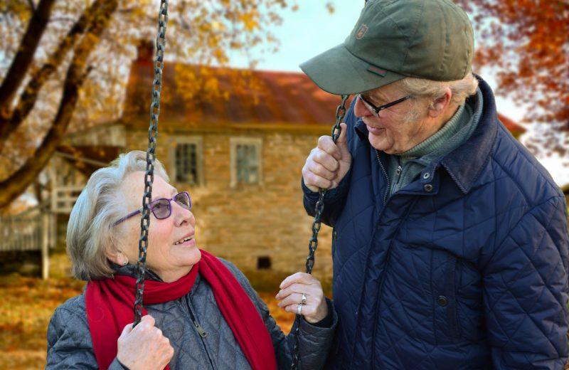 Ouder echtpaar kijkt elkaar liefdevol aan terwijl zij op een schommel zit