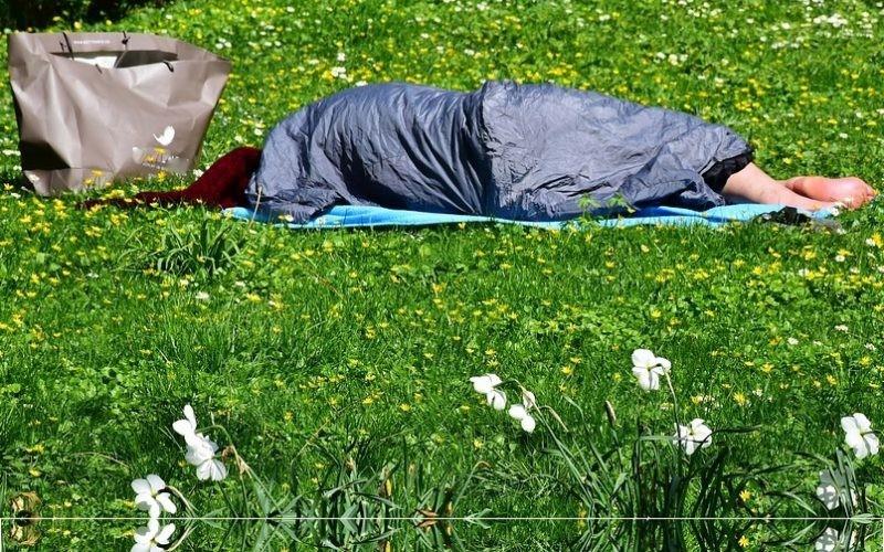 Dakloos persoon slaapt in slaapzak in een veld