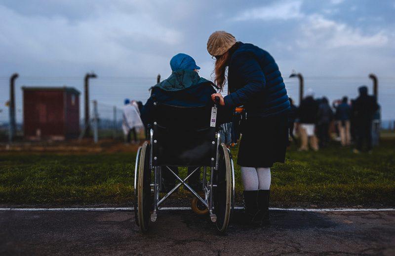 Vrouw in rolstoel kijkt samen met een andere vrouw de verte in