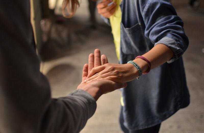 Twee personen reiken elkaar de hand toe
