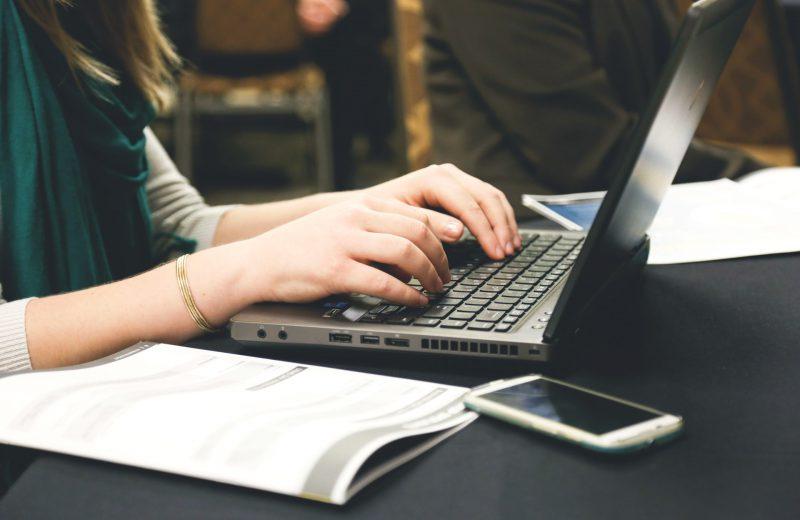 Vrouw zit te werken achter haar laptop